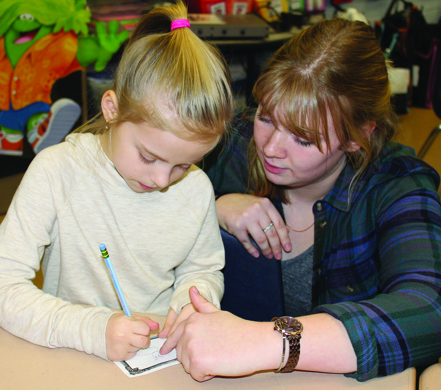 HHS senior Elly Ciesinski guides Hinckley 2nd grader Sophia Schidowka as she creates her own mini artwork.